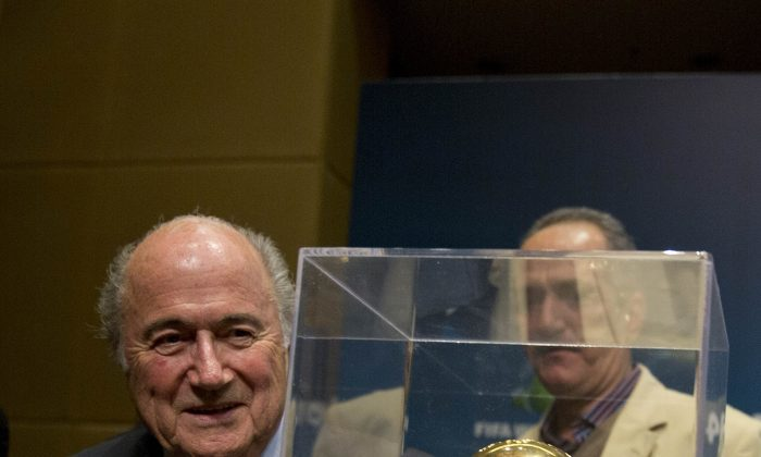 FIFA President Sepp Blatter stands near the World Cup trophy after a press conference, where he talked about the organization and infrastructure of the upcoming World Cup, in Sao Paulo, Brazil, Thursday, June 5, 2014. The World Cup soccer tournament starts on 12 June. (AP Photo/Andre Penner)