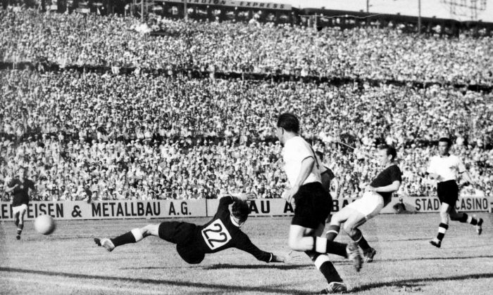 Hungarian forward Nandor Hidegkuti (2nd R) scores the fifth goal for his team past German goalkeeper Heiner Kwiatkowski (22) as Werner Kohlmeyer (C) looks on during the World Cup first-round match between Hungary and West Germany on June 20, 1954 in Basel. Hidegkuti scored twice and his teammate Sandor Kocsis four times as Hungary beat West Germany 8-3. (STAFF/AFP/Getty Images)
