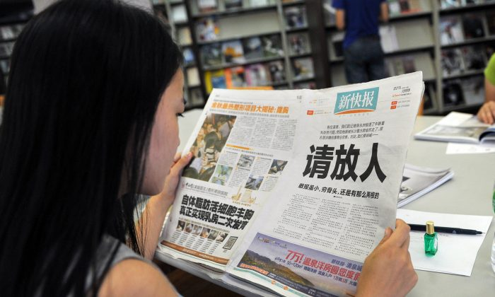 A woman reads the New Express newspaper that carried a full-page editorial with headline 'Please release our man' on Oct. 23, 2013, responding to the punishment of a journalist then. (STR/AFP/Getty Images)