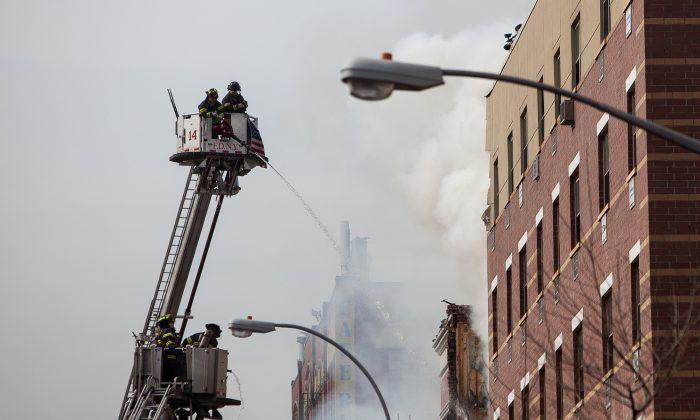 FDNY firefighters tackle the flames after a gas explosion in East Harlem on March 12. (Petr Svab/Epoch Times)
