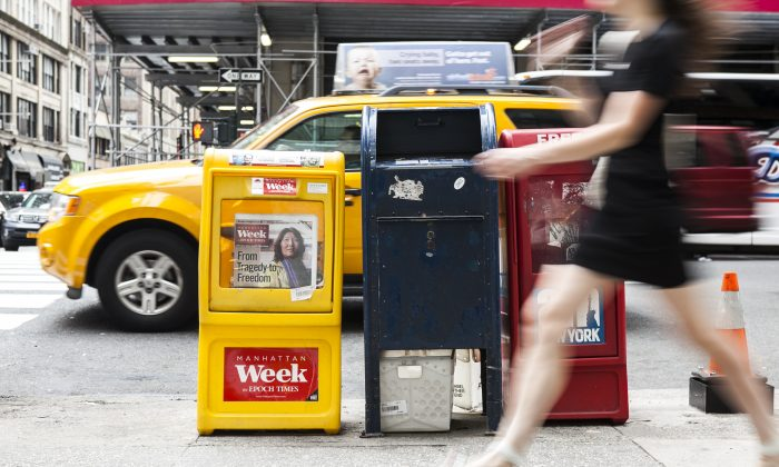 A passerby walks past an Epoch Times box on the streets of Manhattan, on May 19, 2014. Former Congressman Lee Hamilton argues that a vigorous, independent press is necessary for the good health of U.S. democracy. (Samira Bouaou/Epoch Times)