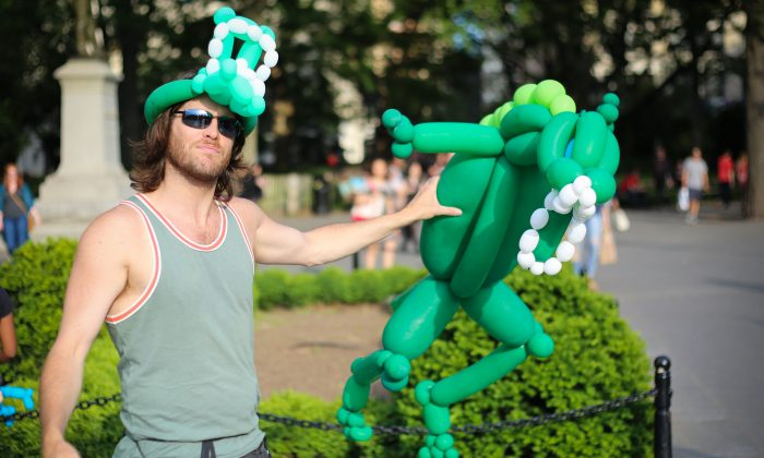John Murdock holds a Godzilla made of several balloons tied ogether in Washington Square Park, New York City on May 30, 2014. (Benjamin Chasteen/Epoch Times)