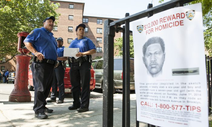 Police near a sign depicting the perpetrator of the stabbing to death of Prince Joshua Avitto, at the Boulevard Housing project in East New York on June 3, 2014. (Samira Bouaou/Epoch Times)
