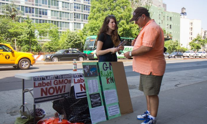 A woman from New York Public Interest Research Group speaks to a passerby about the potential dangers of GMOs in front of a Whole Foods Market in the Lower East Side, New York, on June 3, 2014. (Jonathan Zhou/Epoch Times)