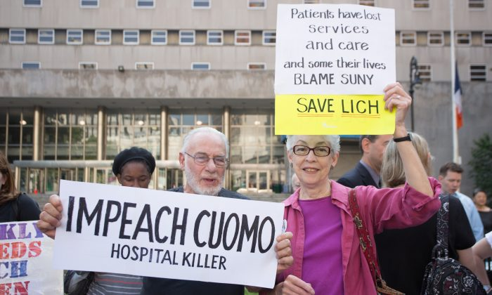 Bob and Brenda Pepper hold signs during a rally to save the Long Island College Hospital from being shut down at the King County Superior Court in the Brooklyn borough of New York City on June 3, 2014. (Laura Cooksey/Epoch Times)
