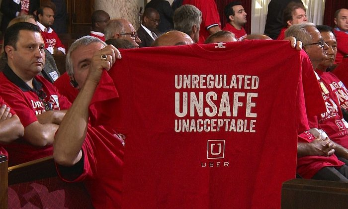 A protester shows a shirt at LA City Council on Tuesday. (Erich Zhang/NTD)