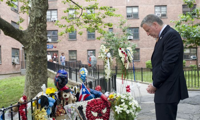 "Mayor Bill de Blasio pauses by the vigil of Prince Joshua ""PJ"" Avitto at the Boulevard Houses in East New York, Brooklyn, on June 11. De Blasio later announced that security cameras would be installed in 49 public housing projects by the end of the year. (Rob Bennett/Mayor's Office)"