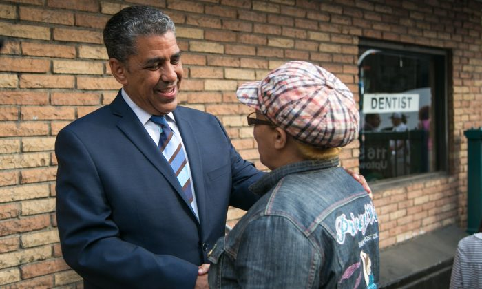 State Sen. Adriano Espaillat, greets commuters in front of the 116th Street subway station in Manhattan, on June 23, 2014. (Benjamin Chasteen/Epoch Times)