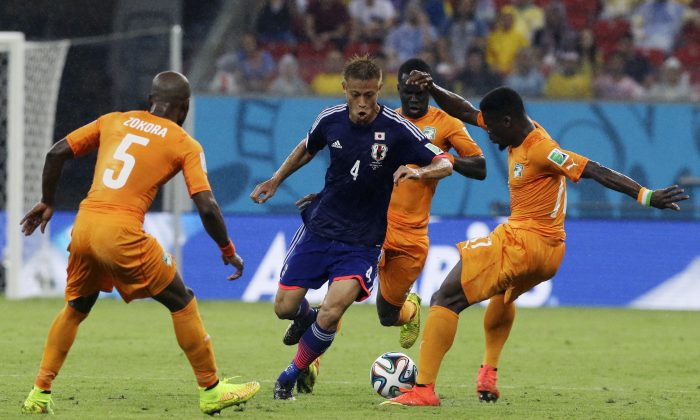 Japan's Keisuke Honda, centre, is crowded out by Ivory Coast's Didier Zokora, left, Serge Aurier, right, and Cheik Tiote during the group C World Cup soccer match between Ivory Coast and Japan at the Arena Pernambuco in Recife, Brazil, Saturday, June 14, 2014.   (AP Photo/Shuji Kajiyama)