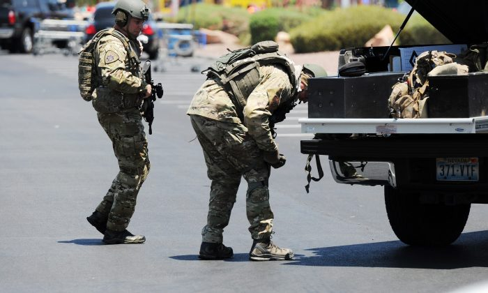 Las Vegas police officers prepare to go near the scene of a shooting in Las Vegas, Sunday, June 8, 2014. The spree began around 11:30 a.m. Sunday when a man and woman walked into CiCi's Pizza and shot two officers who were eating lunch, Las Vegas police spokesman Larry Hadfield said. (AP Photo/Las Vegas Review-Journal, Eric Verduzco)