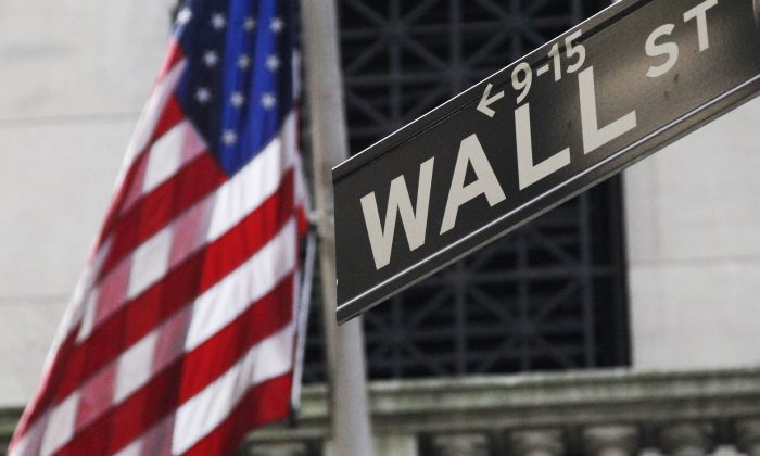 The American flag and Wall St. street sign outside the New York Stock Exchange, in New York, on June 27, 2014. (Mark Lennihan/AP Photo)