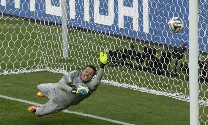 Brazil's goalkeeper Julio Cesar dives for the ball as the decisive penalty hit the goalpost during the World Cup round of 16 soccer match between Brazil and Chile at the Mineirao Stadium in Belo Horizonte, Brazil, Saturday, June 28, 2014. Brazil won 3-2 on penalties after the match ended 1-1 draw after extra-time.   (AP Photo/Hassan Ammar)