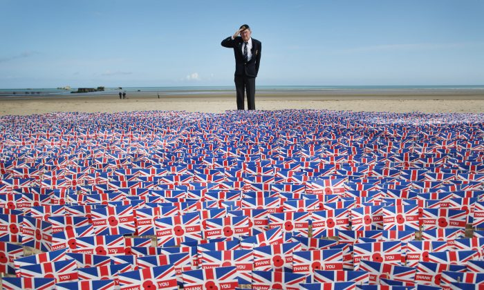WW2 veteran Fred Holborn, from the Fleet Air Arm, salutes as he looks at British Legion Union flags carrying thank you messages planted in the sand on Gold beach on June 5, 2014 near Asnelles, France. 20,000 paper flags are being planted. Each one carries a personal message of Remembrance submitted by Royal British Legion supporters. Friday 6th June is the 70th anniversary of the D-Day landings which saw 156,000 troops from the allied countries including the United Kingdom and the United States join forces to launch an audacious attack on the beaches of Normandy, these assaults are credited with the eventual defeat of Nazi Germany. A series of events commemorating the 70th anniversary are planned for the week with many heads of state travelling to the famous beaches to pay their respects to those who lost their lives. (Peter Macdiarmid/Getty Images)