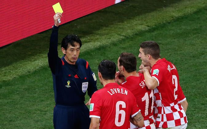 Referee Yuichi Nishimura shows Dejan Lovren of Croatia (2nd L) a yellow card and awards a penalty kick during the 2014 FIFA World Cup Brazil Group A match between Brazil and Croatia at Arena de Sao Paulo on June 12, 2014 in Sao Paulo, Brazil. (Elsa/Getty Images)