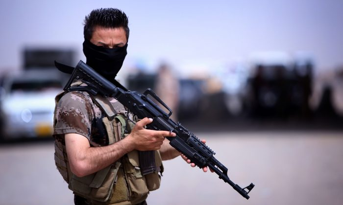 A masked Peshmerga fighter from Iraq's autonomous Kurdish region guards a temporary camp set up to shelter Iraqis fleeing violence in the northern Nineveh province, in Aski kalak, 40 kms west of the region's capital Arbil, on June 13, 2014. Thousands of people who fled Iraq's second city of Mosul after it was overrun by jihadists have been queuing in the blistering heat, hoping to enter the safety of the nearby Kurdish region and furious at Baghdad's failure to help them. (Safin Hamed/AFP/Getty Images)