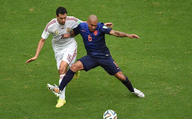 Spain's midfielder Sergio Busquets (L) vies with Netherlands' midfielder Nigel de Jong (R) during a Group B football match between Spain and the Netherlands at the Fonte Nova Arena in Salvador during the 2014 FIFA World Cup on June 13, 2014. (DIMITAR DILKOFF/AFP/Getty Images)