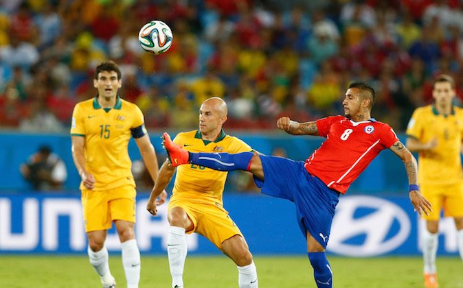 Arturo Vidal of Chile reaches to kick the ball against Mark Bresciano of Australia during the 2014 FIFA World Cup Brazil Group B match between Chile and Australia at Arena Pantanal on June 13, 2014 in Cuiaba, Brazil. (Phil Walter/Getty Images)