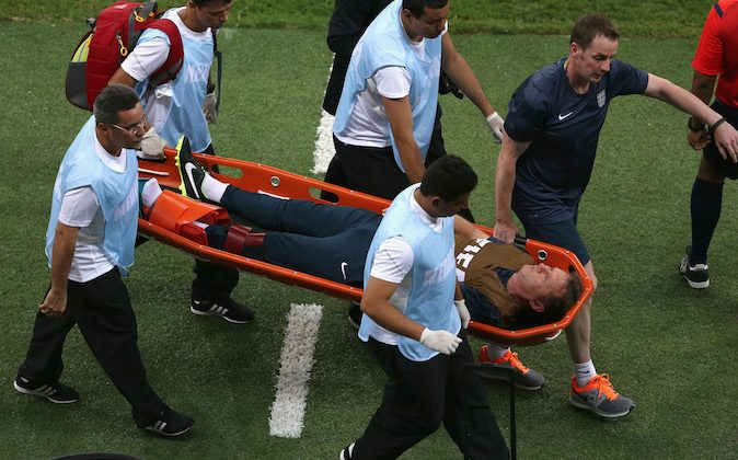 """England trainer Gary Lewin is stretchered off the field after a leg injury during the 2014 FIFA World Cup Brazil Group D match between England and Italy at Arena Amazonia on June 14, 2014 in Manaus, Brazil. (Photo by Warren Little/Getty Images)  England coach Roy Hodgson says """"that was a very sad moment for us. In celebrating the goal he jumped up, landed on a water bottle and dislocated his ankle."""""""