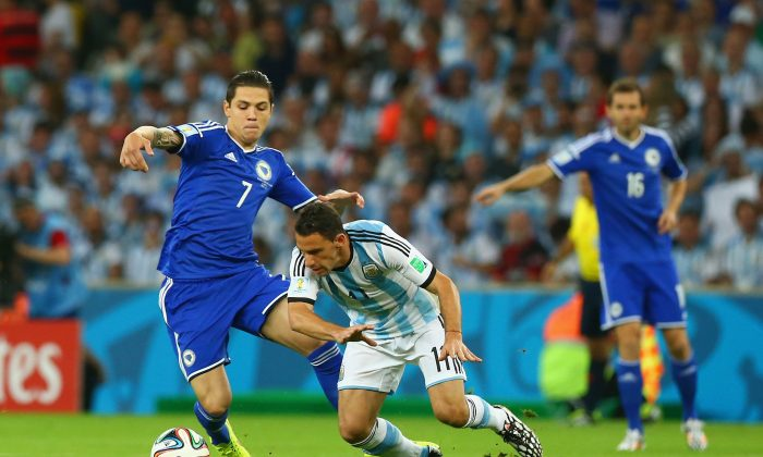 Muhamed Besic of Bosnia and Herzegovina challenges Maxi Rodriguez of Argentina during the 2014 FIFA World Cup Brazil Group F match between Argentina and Bosnia-Herzegovina at Maracana on June 15, 2014 in Rio de Janeiro, Brazil. (Ronald Martinez/Getty Images)