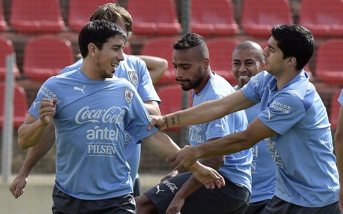 Uruguay's forward Luis Suarez (R) plays with defender Jorge Fucile (L) while midfielder Alvaro Pereira (2-L) and midfielder Walter Gargano look on during a training session at Arena do Jacare in Sete Lagoas, Minas Gerais on June 17, 2014. Uruguay is preparing for its second match of Group D of the FIFA World Cup 2014 in Brazil, in which they will face England at Corinthians Arena in Sao Paulo on June 19, 2014.   (DANIEL GARCIA/AFP/Getty Images)