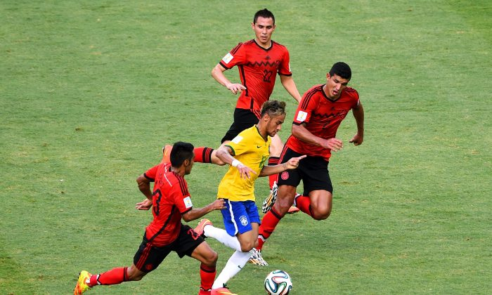 Neymar of Brazil controls the ball against Jose Juan Vazquez (L) and Francisco Javier Rodriguez of Mexico (R) during the 2014 FIFA World Cup Brazil Group A match between Brazil and Mexico at Castelao on June 17, 2014 in Fortaleza, Brazil. (Jamie McDonald/Getty Images)