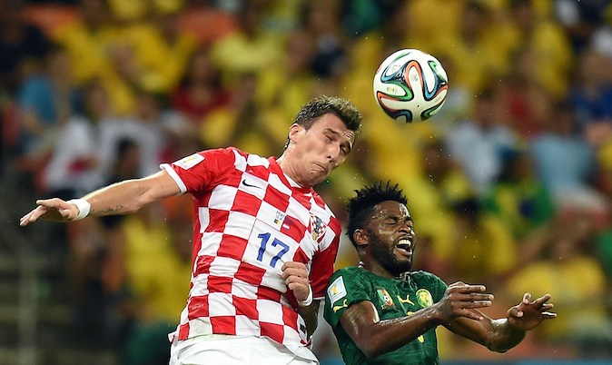 Croatia's forward Mario Mandzukic (L) heads the ball past Cameroon's defender Nicolas Nkoulou during the Group A football match between Cameroon and Croatia at The Amazonia Arena in Manaus on June 18, 2014, during the 2014 FIFA World Cup. (JAVIER SORIANO/AFP/Getty Images)