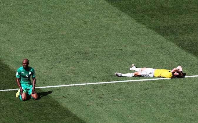 James Rodriguez of Colombia lies on the field after a teammates missed chance as Didier Zokora of the Ivory Coast looks on during the 2014 FIFA World Cup Brazil Group C match between Colombia and Cote D'Ivoire at Estadio Nacional on June 19, 2014 in Brasilia, Brazil. (Photo by Adam Pretty/Getty Images)