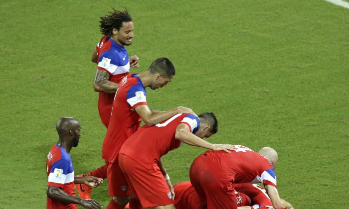 United States' John Brooks is mobbed by his teammates after scoring their side's second goal during the group G World Cup soccer match between Ghana and the United States at the Arena das Dunas in Natal, Brazil, Monday, June 16, 2014. The United States defeated Ghana 2-1. (AP Photo/Hassan Ammar)