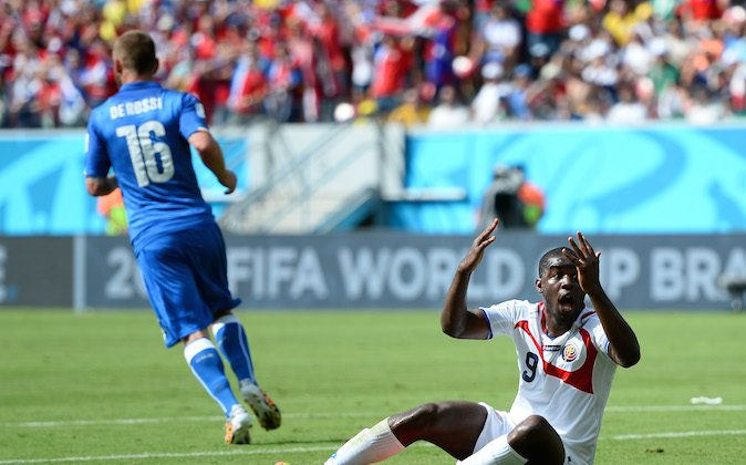 Joel Campbell of Costa Rica reacts after a challenge by Giorgio Chiellini and Andrea Barzagli (not pictured) of Italy during the 2014 FIFA World Cup Brazil Group D match between Italy and Costa Rica at Arena Pernambuco on June 20, 2014 in Recife, Brazil. (Jamie McDonald/Getty Images)