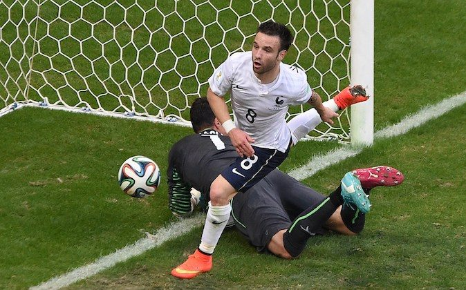 France's midfielder Mathieu Valbuena (top) runs past Switzerland's goalkeeper Diego Benaglio after scoring his team's third goal during a Group E football match between Switzerland and France at the Fonte Nova Arena in Salvador during the 2014 FIFA World Cup on June 20, 2014. (DIMITAR DILKOFF/AFP/Getty Images)