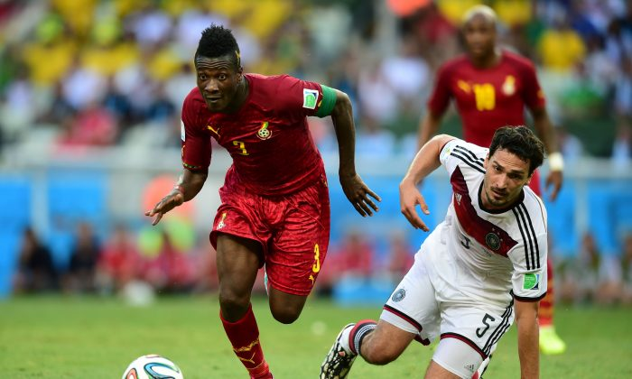 Ghana's forward and captain Asamoah Gyan (L) vies with Germany's defender Mats Hummels during a Group G football match between Germany and Ghana at the Castelao Stadium in Fortaleza during the 2014 FIFA World Cup on June 21, 2014. (JAVIER SORIANO/AFP/Getty Images)