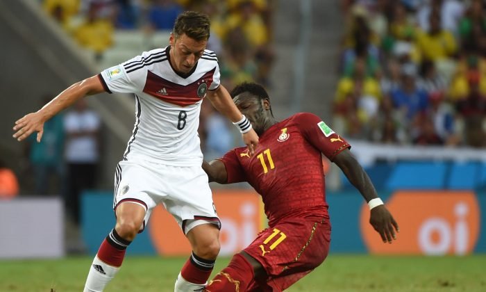 Germany's midfielder Mesut Ozil (L) vies with Ghana's midfielder Sulley Ali Muntari during a Group G football match between Germany and Ghana at the Castelao Stadium in Fortaleza during the 2014 FIFA World Cup on June 21, 2014. (PATRIK STOLLARZ/AFP/Getty Images)