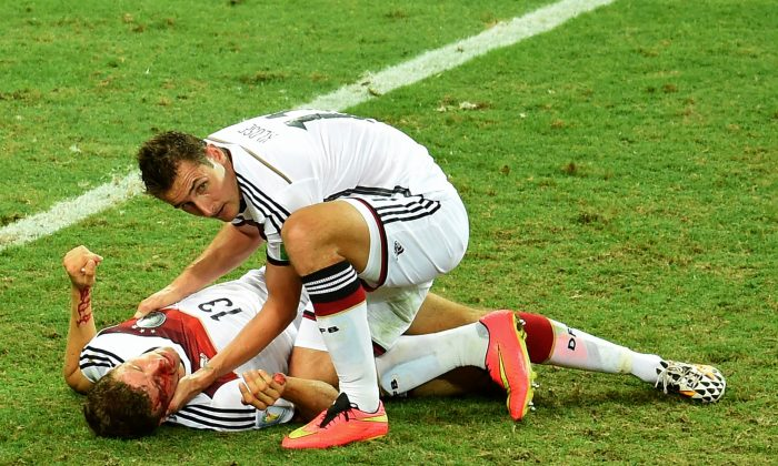 Germany's forward Miroslav Klose (R) checks Germany's forward Thomas Mueller after a collision during a Group G football match between Germany and Ghana at the Castelao Stadium in Fortaleza during the 2014 FIFA World Cup on June 21, 2014. The game ended with a draw 2-2.  (EMMANUEL DUNAND/AFP/Getty Images)