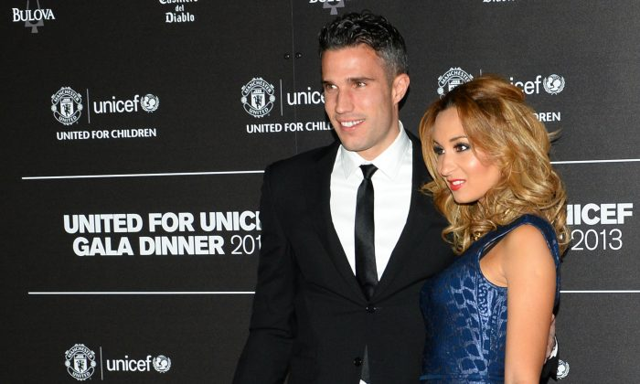 Manchester United's Dutch striker Robin van Persie (L) and his wife Bouchra pose for photographs as the arrive for a gala dinner in aid of UNICEF at Old Trafford in Manchester on November 21, 2013. (PAUL ELLIS/AFP/Getty Images)