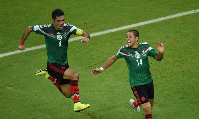 Mexico's defender and captain Rafael Marquez (L) celebrates with Mexico's forward Javier Hernandez after Marquez headed his team's first goal during a Group A football match between Croatia and Mexico at the Pernambuco Arena in Recife during the 2014 FIFA World Cup on June 23, 2014. (JAVIER SORIANO/AFP/Getty Images)