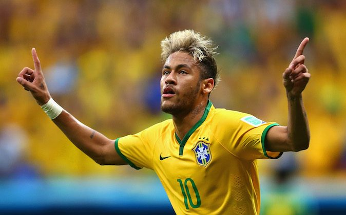 Neymar of Brazil celebrates scoring his team's second goal and his second of the game during the 2014 FIFA World Cup Brazil Group A match between Cameroon and Brazil at Estadio Nacional on June 23, 2014 in Brasilia, Brazil. (Clive Brunskill/Getty Images)