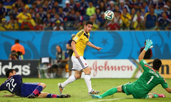 James Rodriguez of Colombia shoots and scores his team's fourth goal past goalkeeper Eiji Kawashima of Japan during the 2014 FIFA World Cup Brazil Group C match between Japan and Colombia at Arena Pantanal on June 24, 2014 in Cuiaba, Brazil. (Photo by Adam Pretty/Getty Images)