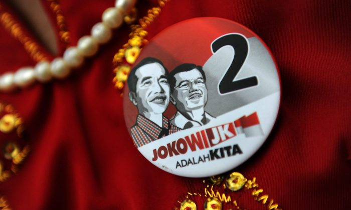 A supporter of Indonesian frontrunner presidential candidate Joko Widodo (L-portrait), representing a region and wearing pin bearing his portrait and running mate Jusuf Kalla (R-portrait), attends a campaign rally in Jakarta on June 25, 2014. The popularity gap between Widodo and opponent Prabowo Subianto, a former general narrowed as the campaign race for the July 9 presidential election heats up. (Romeo Gacad/AFP/Getty Images)