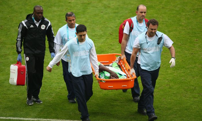 Michael Babatunde of Nigeria is stretchered off the field with his right arm wrapped during the 2014 FIFA World Cup Brazil Group F match between Nigeria and Argentina at Estadio Beira-Rio on June 25, 2014 in Porto Alegre, Brazil. (Photo by Quinn Rooney/Getty Images)
