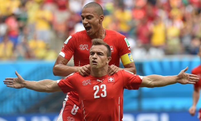 Switzerland's midfielder Xherdan Shaqiri celebrates with midfielder Goekhan Inler (back) after scoring a goal during the Group E football match between Honduras and Switzerland at the Amazonia Arena in Manaus during the 2014 FIFA World Cup on June 25, 2014. (RODRIGO ARANGUA/AFP/Getty Images)
