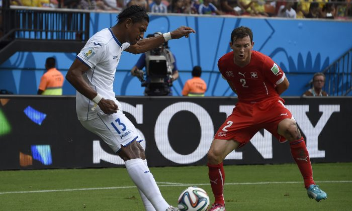 Honduras' forward Carlo Costly (L) vies with Switzerland's defender Stephan Lichtsteiner during a Group E football match between Honduras and Switzerland at the Amazonia Arena in Manaus during the 2014 FIFA World Cup on June 25, 2014. (JUAN BARRETO/AFP/Getty Images)