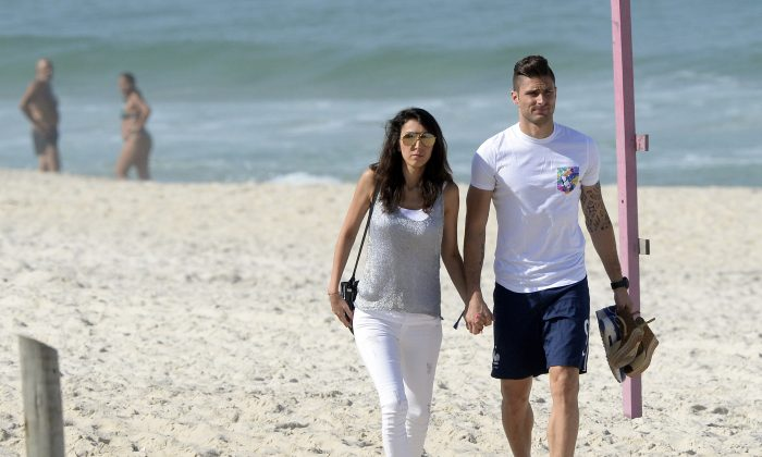 France's forward Olivier Giroud and his wife Jennifer Giroud walk on a beach in Rio de Janeiro during the 2014 FIFA World Cup football tournament on June 26, 2014. (FRANCK FIFE/AFP/Getty Images)