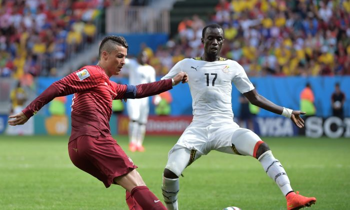 Portugal's forward and captain Cristiano Ronaldo (L) and Ghana's midfielder Mohammed Rabiu vie during the Group G football match between Portugal and Ghana at the Mane Garrincha National Stadium in Brasilia during the 2014 FIFA World Cup on June 26, 2014. (GABRIEL BOUYS/AFP/Getty Images)