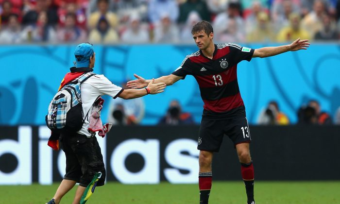 A pitch invader interacts with Thomas Mueller of Germany during the 2014 FIFA World Cup Brazil group G match between the United States and Germany at Arena Pernambuco on June 26, 2014 in Recife, Brazil. (Michael Steele/Getty Images)