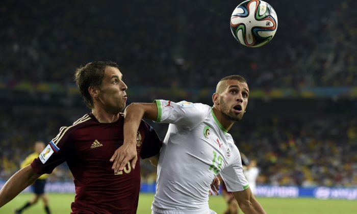 Russia's defender Dmitry Kombarov (L) challenges Algeria's forward Islam Slimani for the ball during the Group H football match between Algeria and Russia at The Baixada Arena in Curitiba on June 26, 2014, during the 2014 FIFA World Cup. (PHILIPPE DESMAZES/AFP/Getty Images)