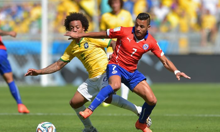 Alexis Sanchez of Chile and Marcelo of Brazil compete for the ball during the 2014 FIFA World Cup Brazil round of 16 match between Brazil and Chile at Estadio Mineirao on June 28, 2014 in Belo Horizonte, Brazil. (Buda Mendes/Getty Images)