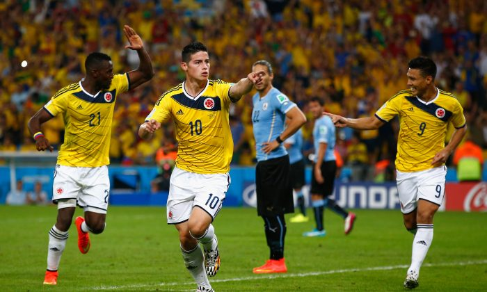 James Rodriguez of Colombia (C) celebrates scoring his team's second goal and his second of the game with teammates Jackson Martinez (L) and Teofilo Gutierrez during the 2014 FIFA World Cup Brazil round of 16 match between Colombia and Uruguay at Maracana on June 28, 2014 in Rio de Janeiro, Brazil. (Clive Rose/Getty Images)