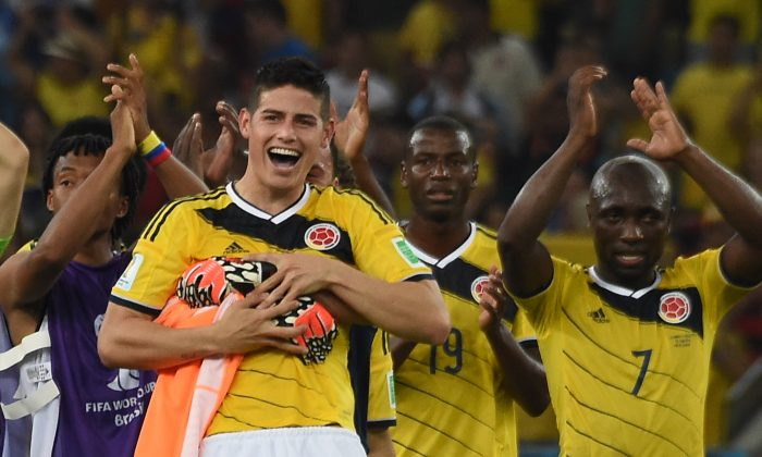 Colombia's midfielder James Rodriguez and his teammates celebrate after the Round of 16 football match between Colombia and Uruguay at the Maracana Stadium in Rio de Janeiro during the 2014 FIFA World Cup in Brazil on June 28, 2014. (LUIS ACOSTA/AFP/Getty Images)