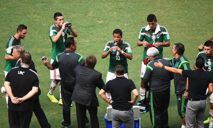 Mexico players take on fluids during a cooling break in the 2014 FIFA World Cup Brazil Round of 16 match between Netherlands and Mexico at Castelao on June 29, 2014 in Fortaleza, Brazil. (Jamie McDonald/Getty Images)