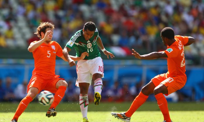 Giovani dos Santos of Mexico shoots and scores his team's first goal against Daley Blind (L) and Georginio Wijnaldum of the Netherlands during the 2014 FIFA World Cup Brazil Round of 16 match between Netherlands and Mexico at Castelao on June 29, 2014 in Fortaleza, Brazil. (Michael Steele/Getty Images)